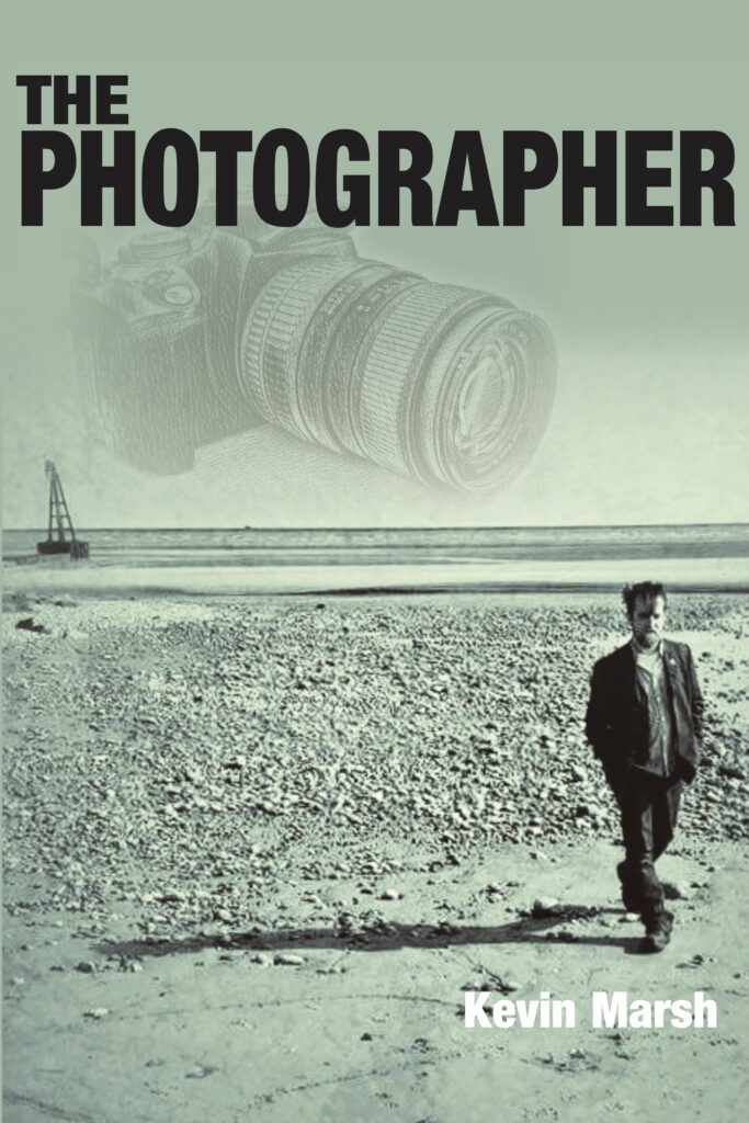 Softback cover showing camera and a lone figure on a beach with the tide out